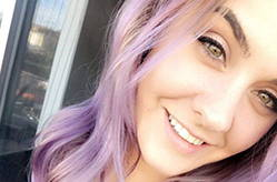 Close up of Felicia smiling into the camera with purple hair and eyeliner.