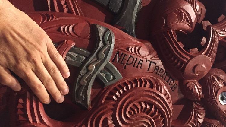A hand placed respectfully on a Māori carving.