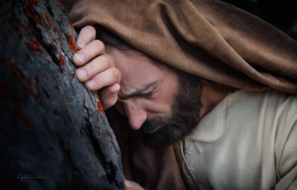Up-close Gethsemane picture of Jesus suffering as he leans against a tree.