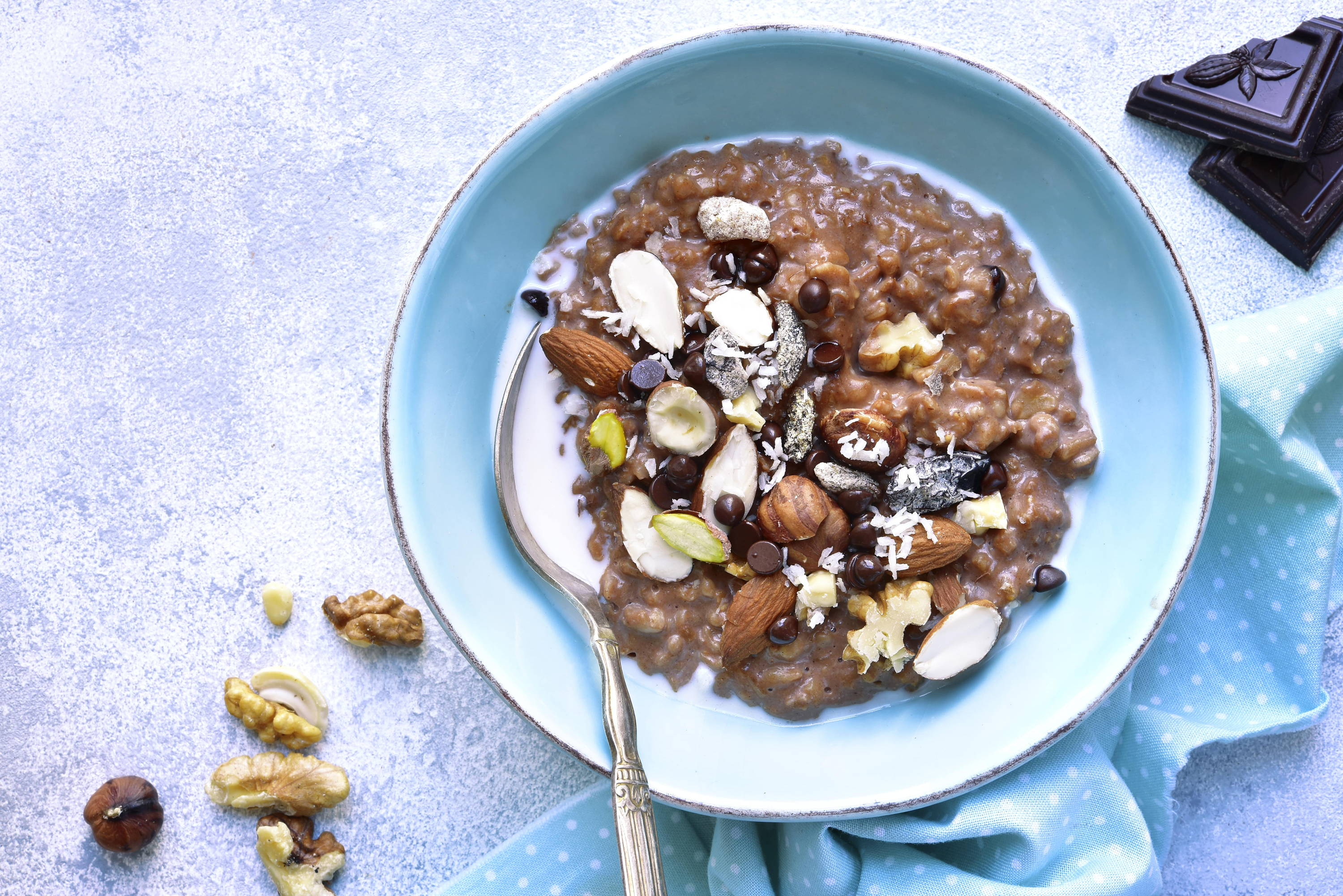 Vegan chocolate overnight oats with almonds and hazelnuts in a blue bowl