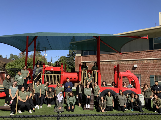 All of our teachers posing on our firetruck play structure during teacher in service day