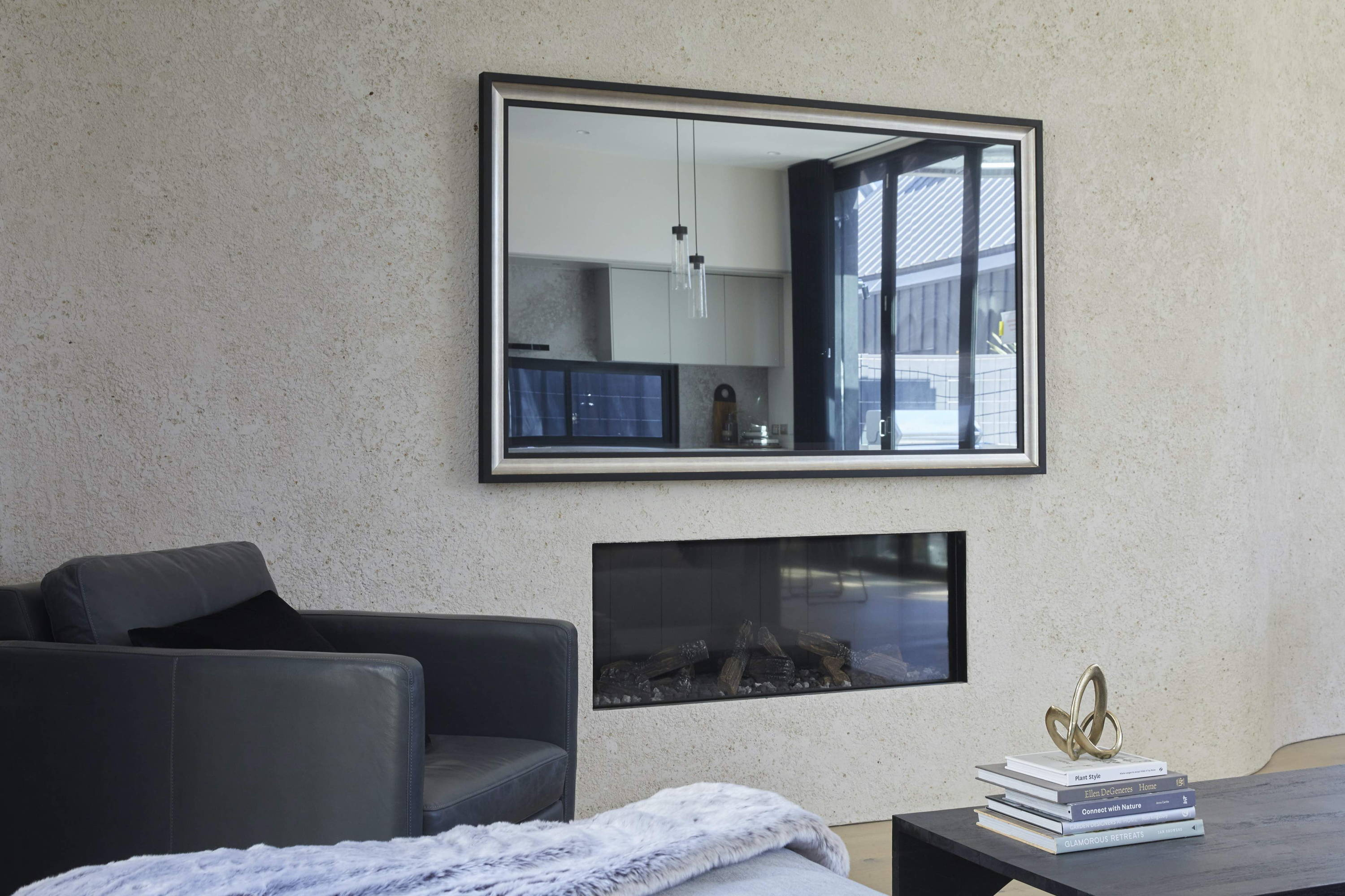 A TV-Mirror hanging on the wall of a coastal, elegant bedroom setting
