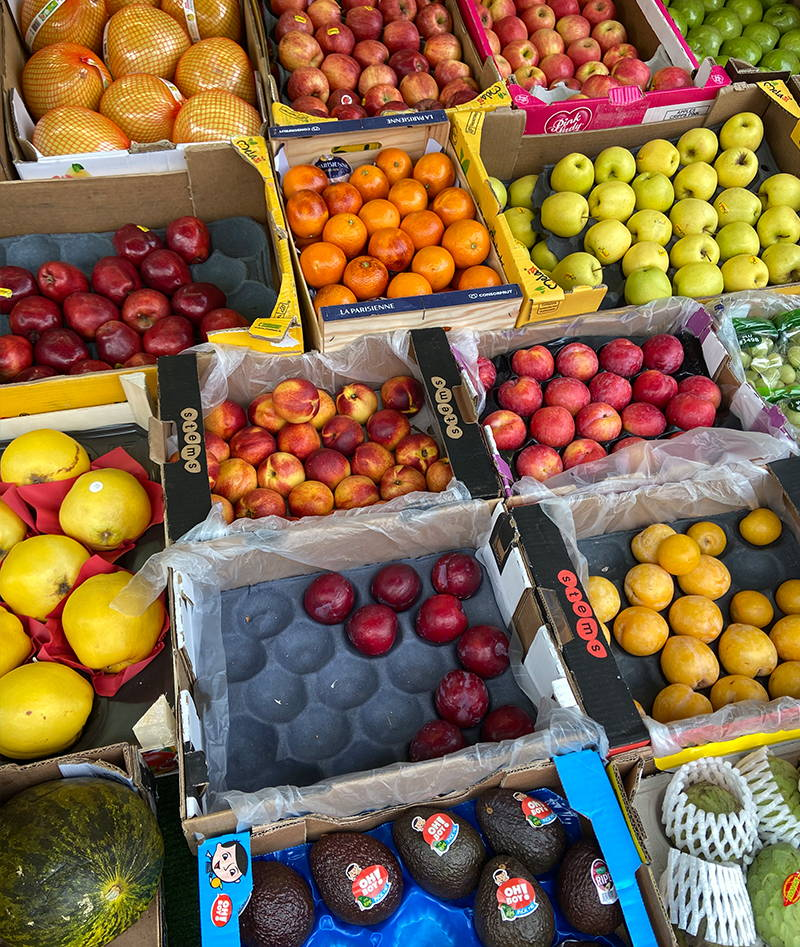Avacados, plums, and nectarines on a market stall
