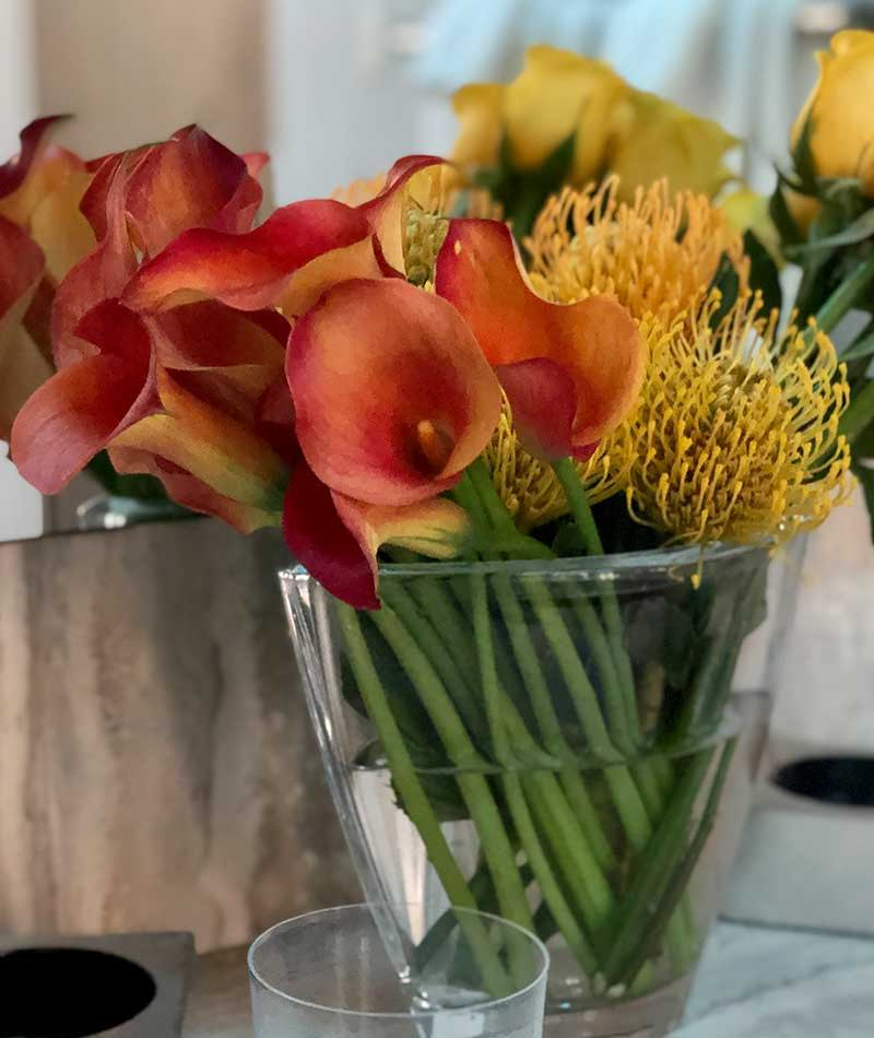 Orange and yellow arrangement of Calla Lilies and Pincushion next to a mirror