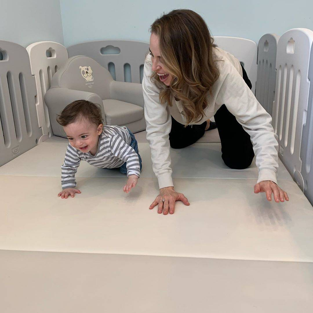 baby and mom playing on playmat