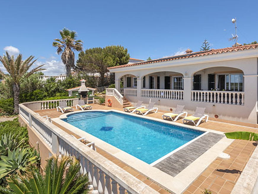 Hondarribia, Spain - Located on the rocky south coast of Menorca, this Mediterranean-style villa is on the market for 650,000 euros. The residence affords three bedrooms, two bathrooms, and a living room with a dining area. The outdoor highlights include several different terraces and a garden with a pool.