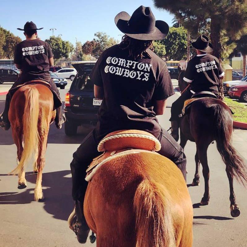 The Compton Cowboys riding on horseback through urban environment