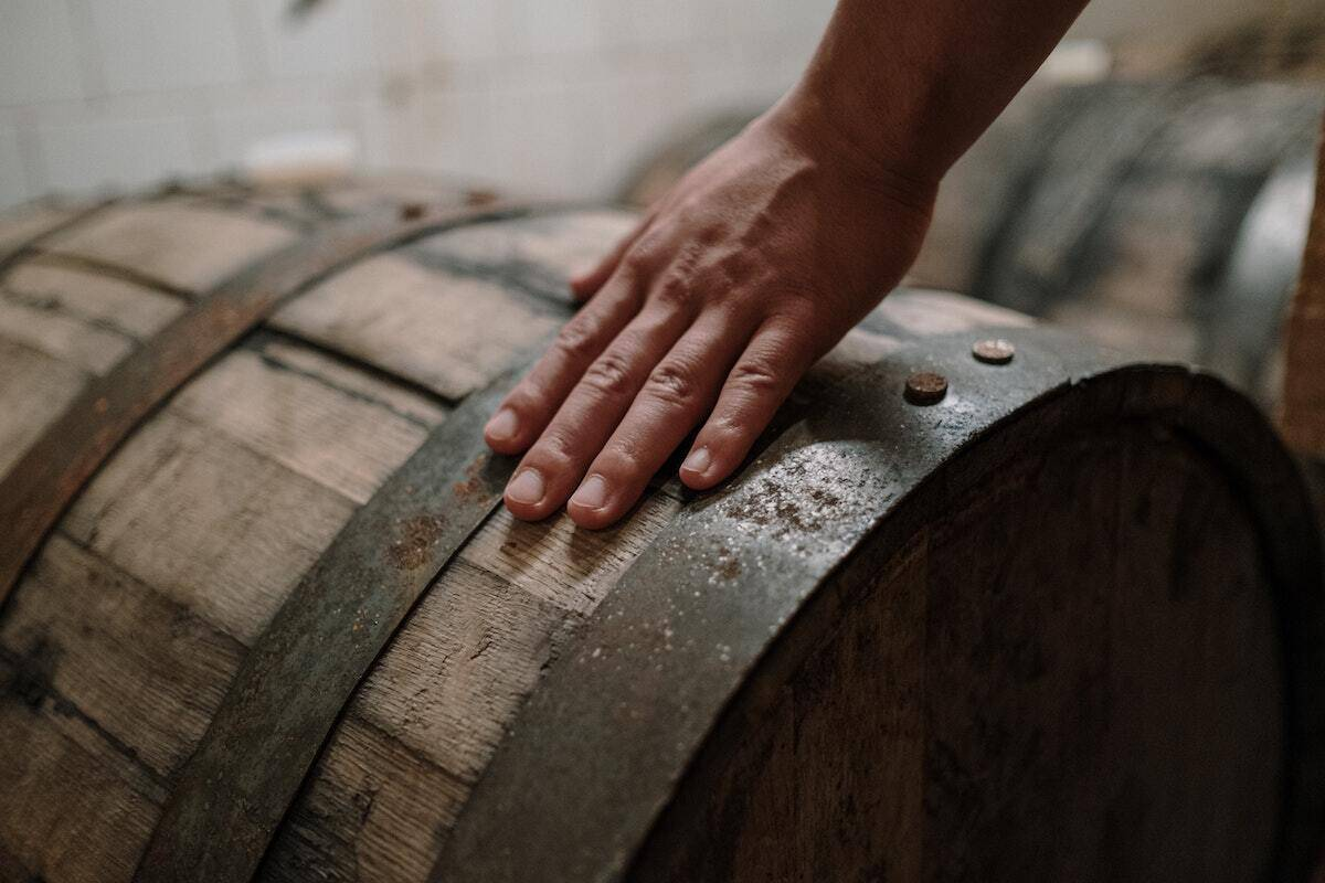 Hand on a barrel demonstrating the importance of the fermentation phase that create the flavours in the wine.