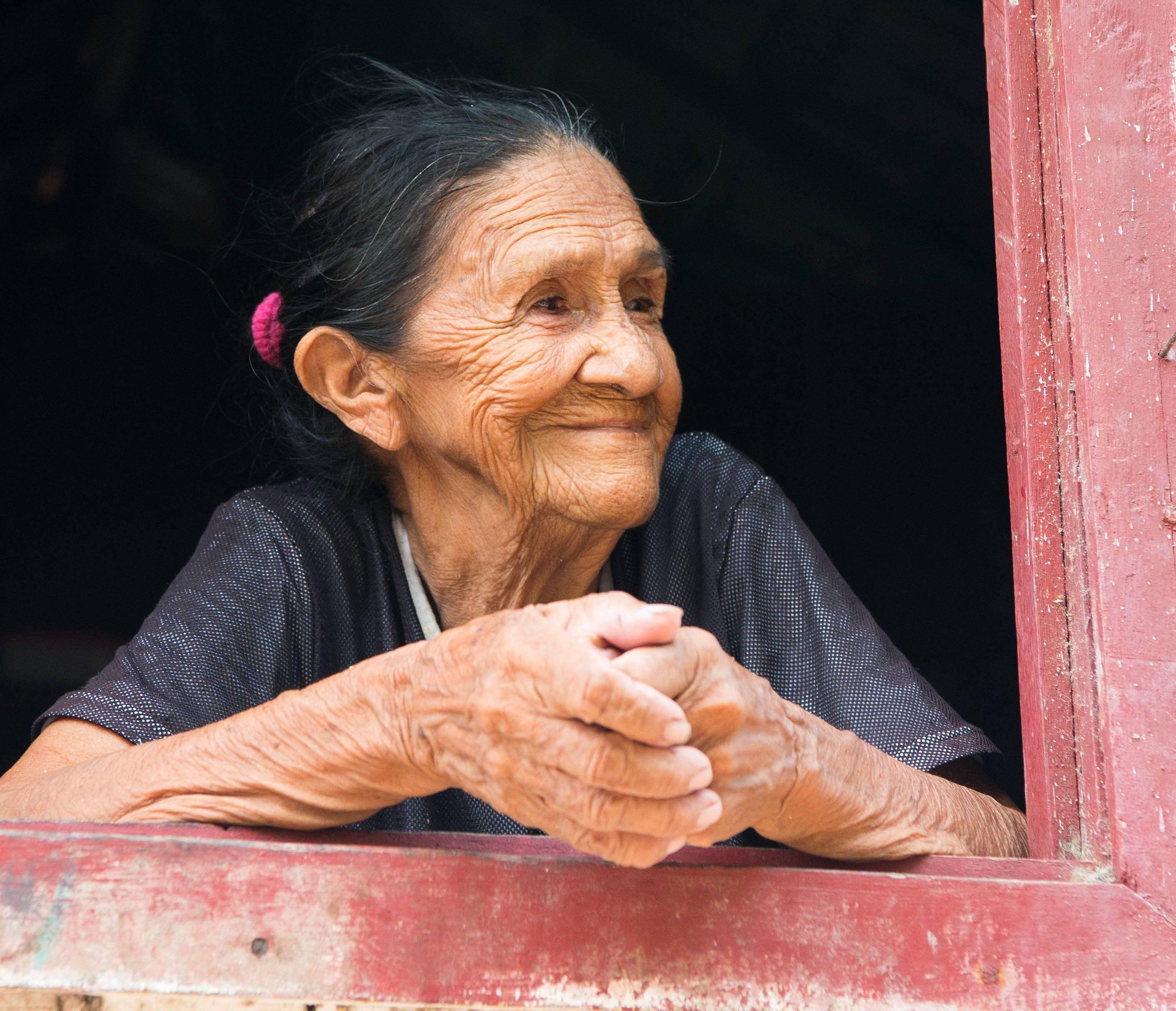 Elderly Brazilian woman gazing out of window