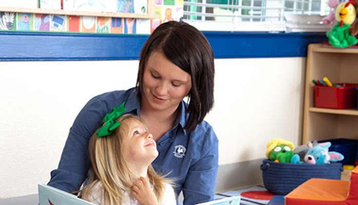 Young Primrose student looks up at her teacher as she sits on her lap
