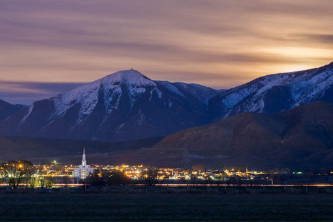 Distant photo of the Payson Utah Temple glowing amid city lights beneath the mountains