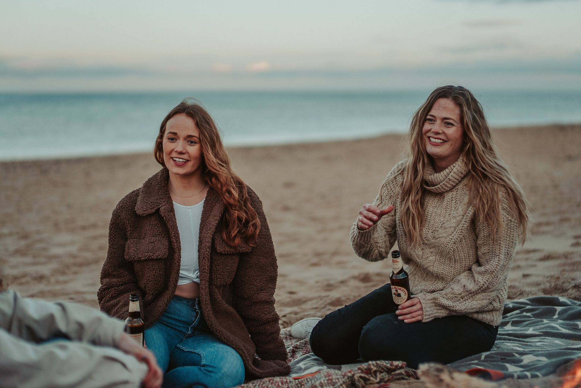 Image of two girls laughing on beach