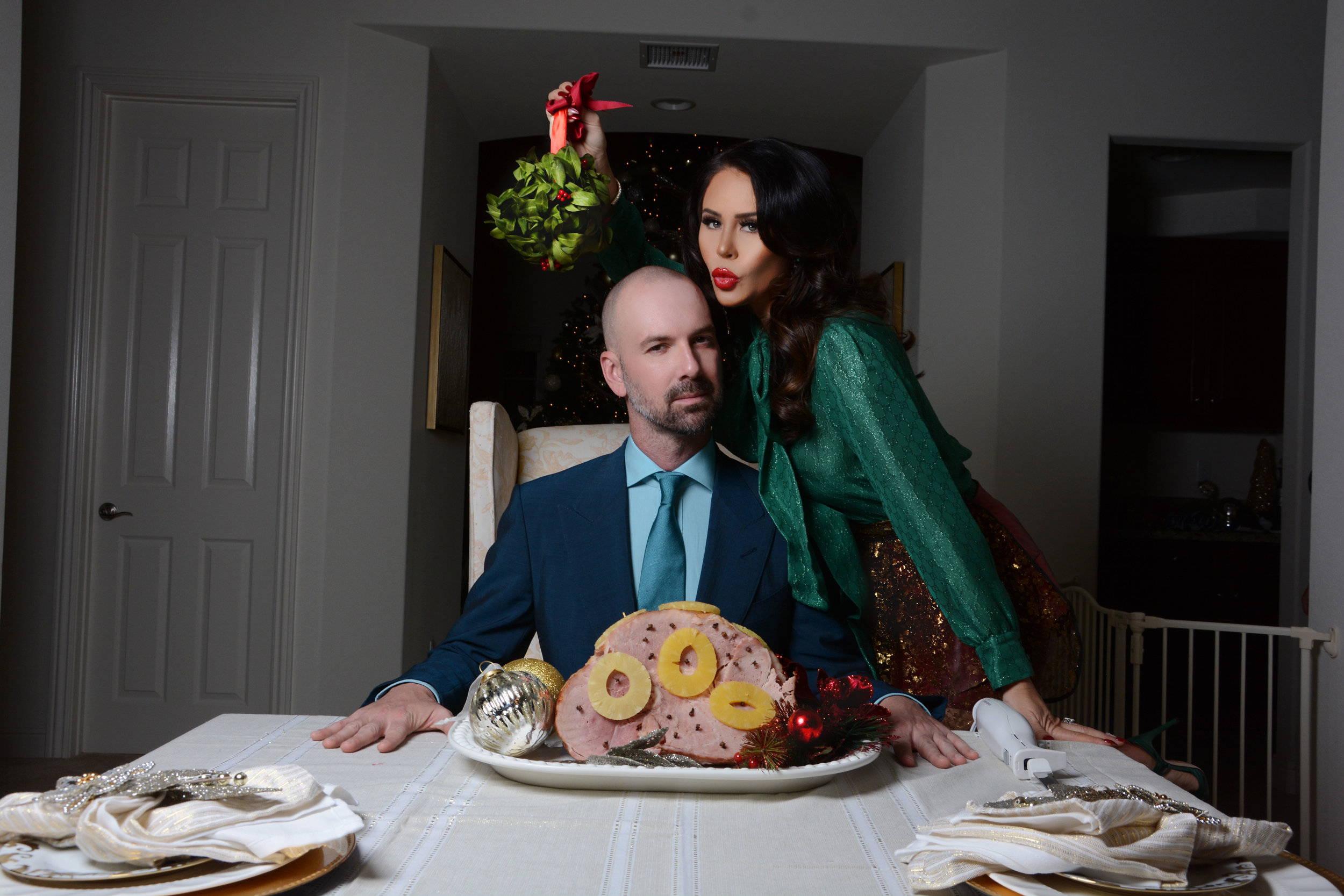 Dr. Barczak and Lea with Christmas ham under the mistletoe