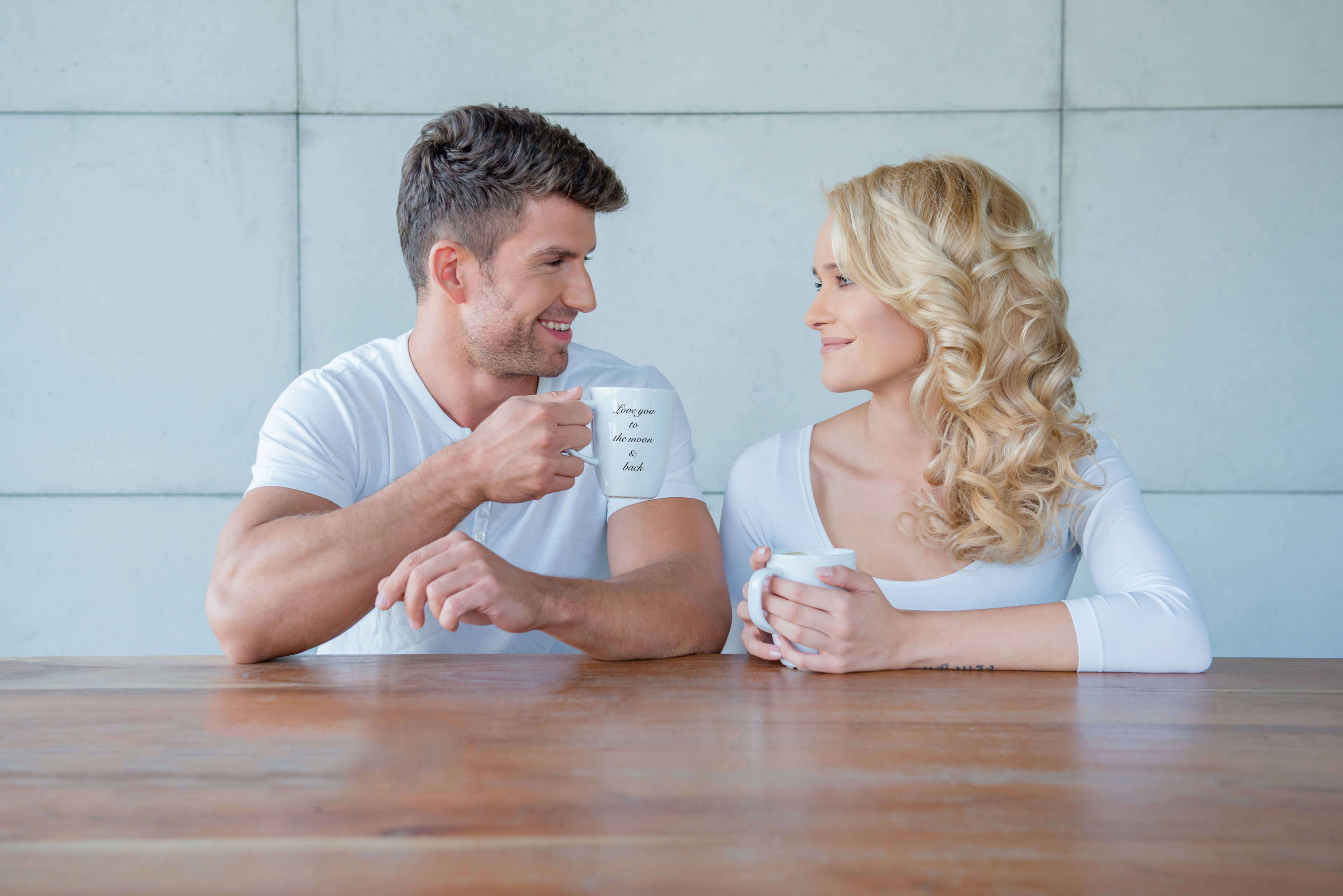 a couple taking there morning coffee in special custom mugs