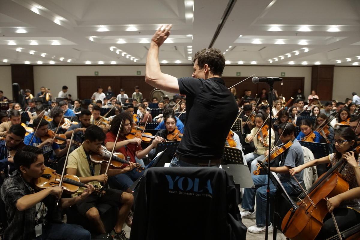 Sonriente director de orquesta con su orquesta completa de estudiantes de YOLA se preparan para una actuación