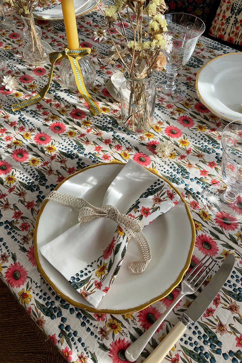 Close up of tablescape featuring YOLKE's wildflower napkins wrapped in lace