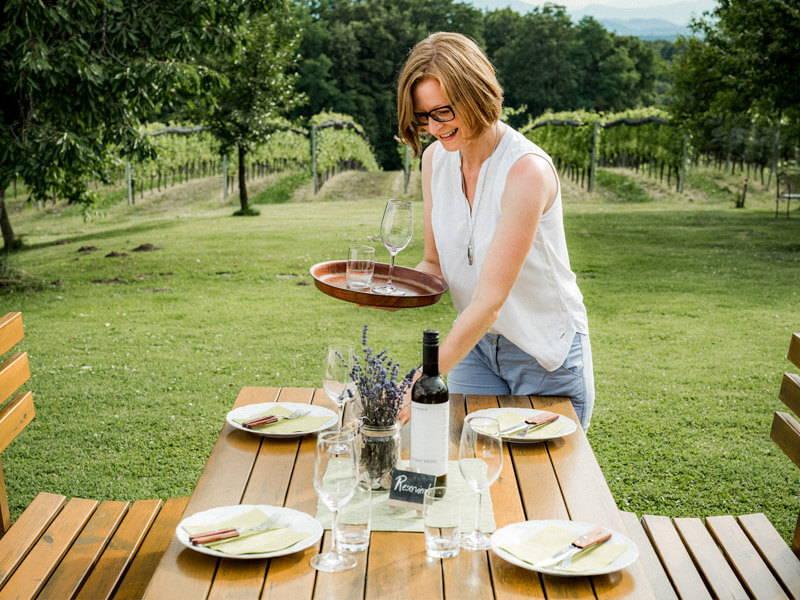 Elisabeth Trummer deckt den Buschenschank-Tisch im Freien vor dem Weingarten.