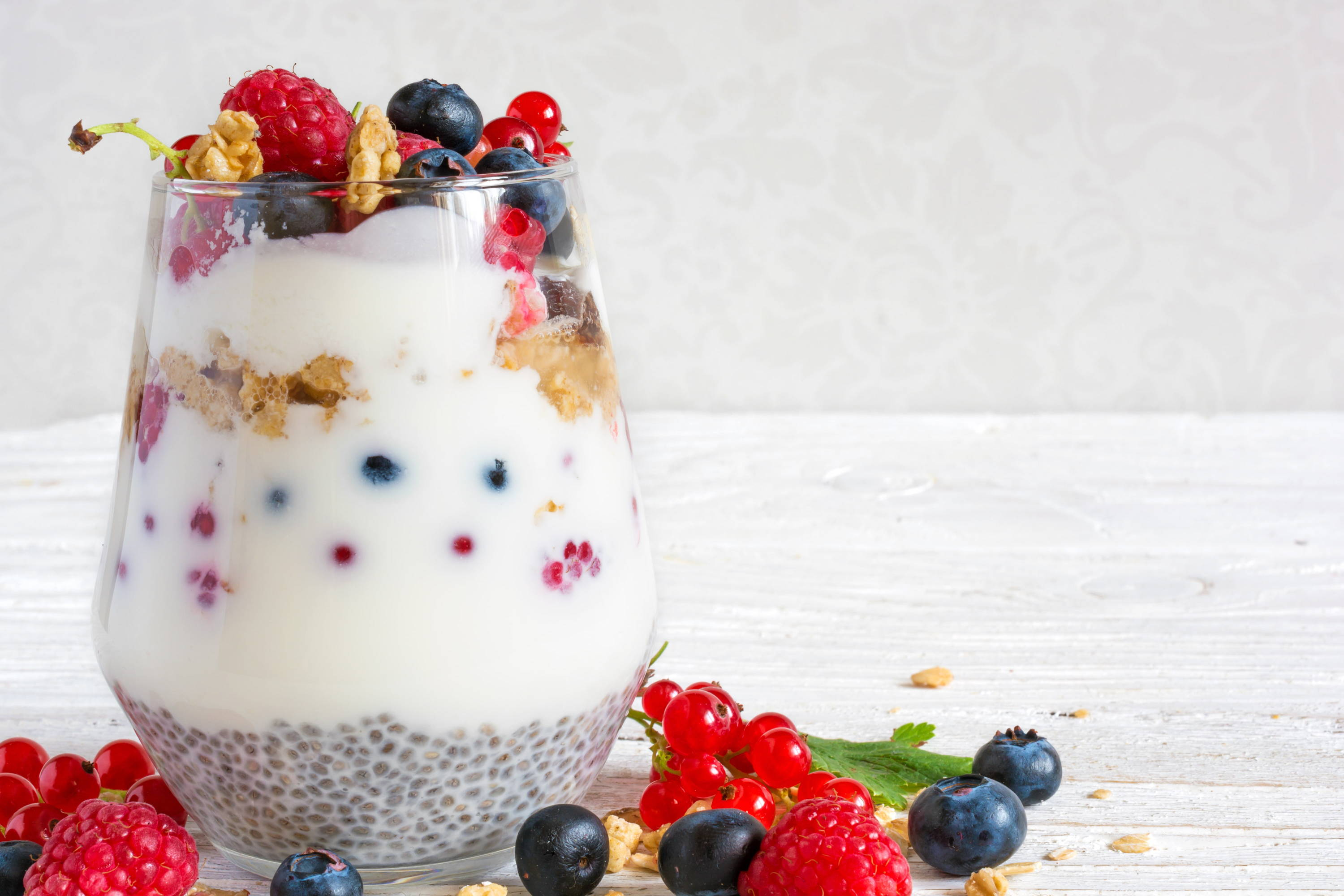 Vegan healthy oats, granola and chia seed pudding with yoghurt and berries in a glass jar.