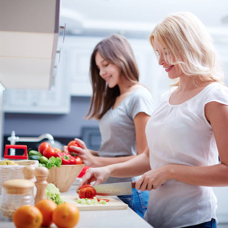 two ladies cutting red tomatoes on a cutting board