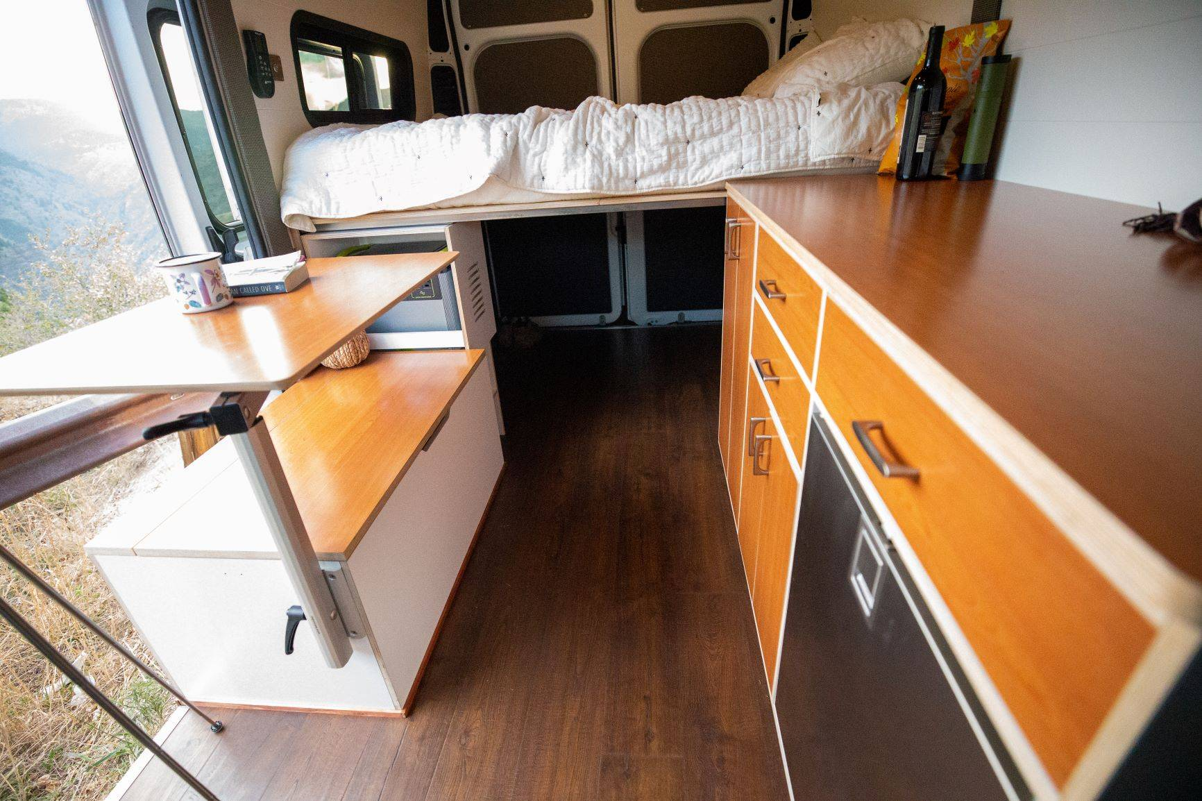 The Bivy - Sprinter 144 / ProMaster 136 Van Conversion - Interior View of Cabinets, Galley, Floor-Mount Table and Bed - The Vansmith