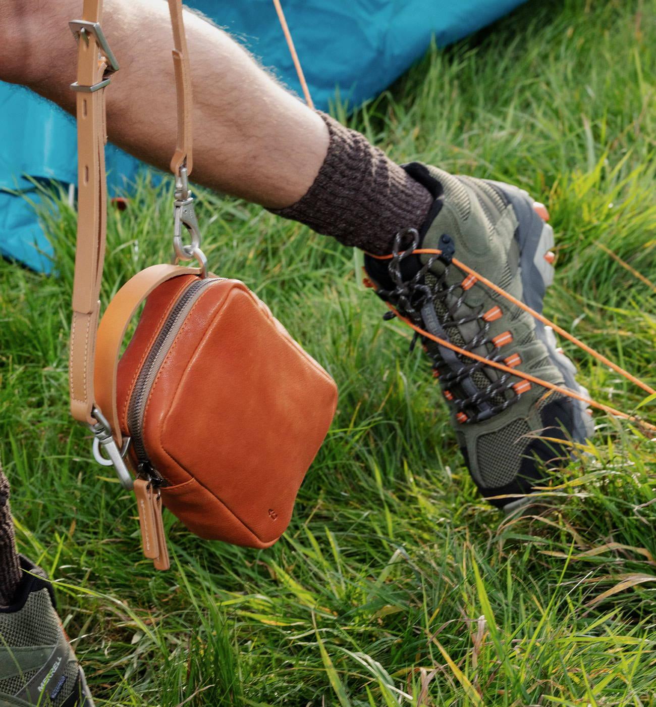 Model carrying Hurley Calvert Leather Crossbody Bag in Tan