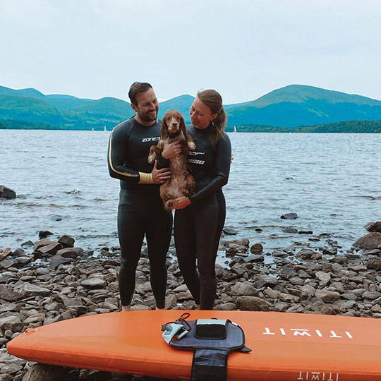 dog with paws up on standup paddle board