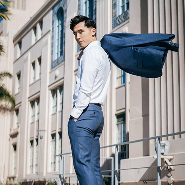 profile shot asian man wearing slim white dress shirt with blazer over shoulder