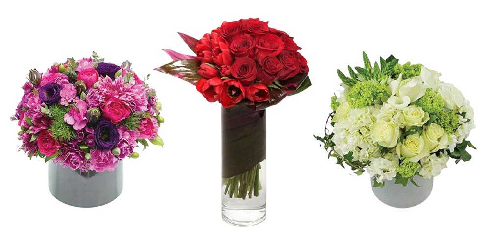 Picture of three medium size arrangements in a ceramic and glass vase with colorful flowers