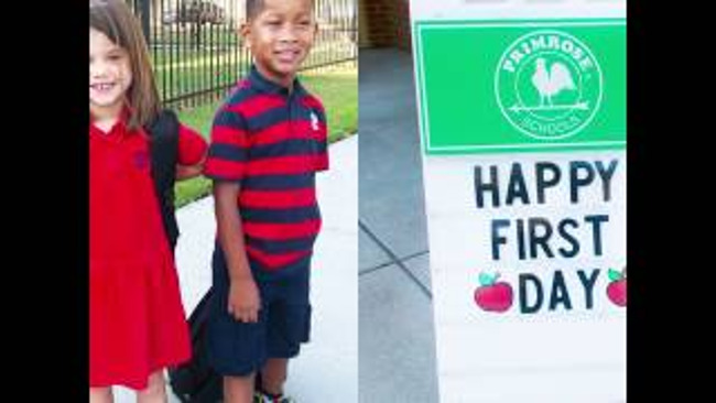Two young and smiling Primrose students stand next to a happy first day of school poster
