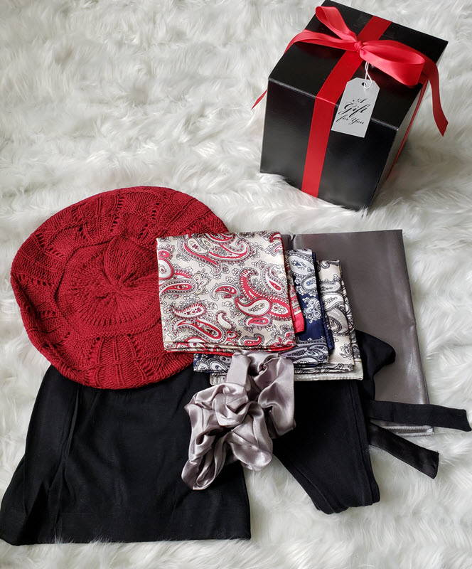 A photo showcasing the gift box packaging and each product in the bundle: satin lined beret hat, satin lined beanie hat, headband with satin lining, satin scrunchies, satin bandannas and satin headrest square.