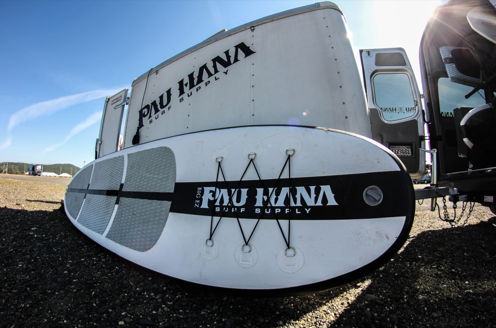 pau hana surf supply big ez inflatable sup board next to a van and trailer