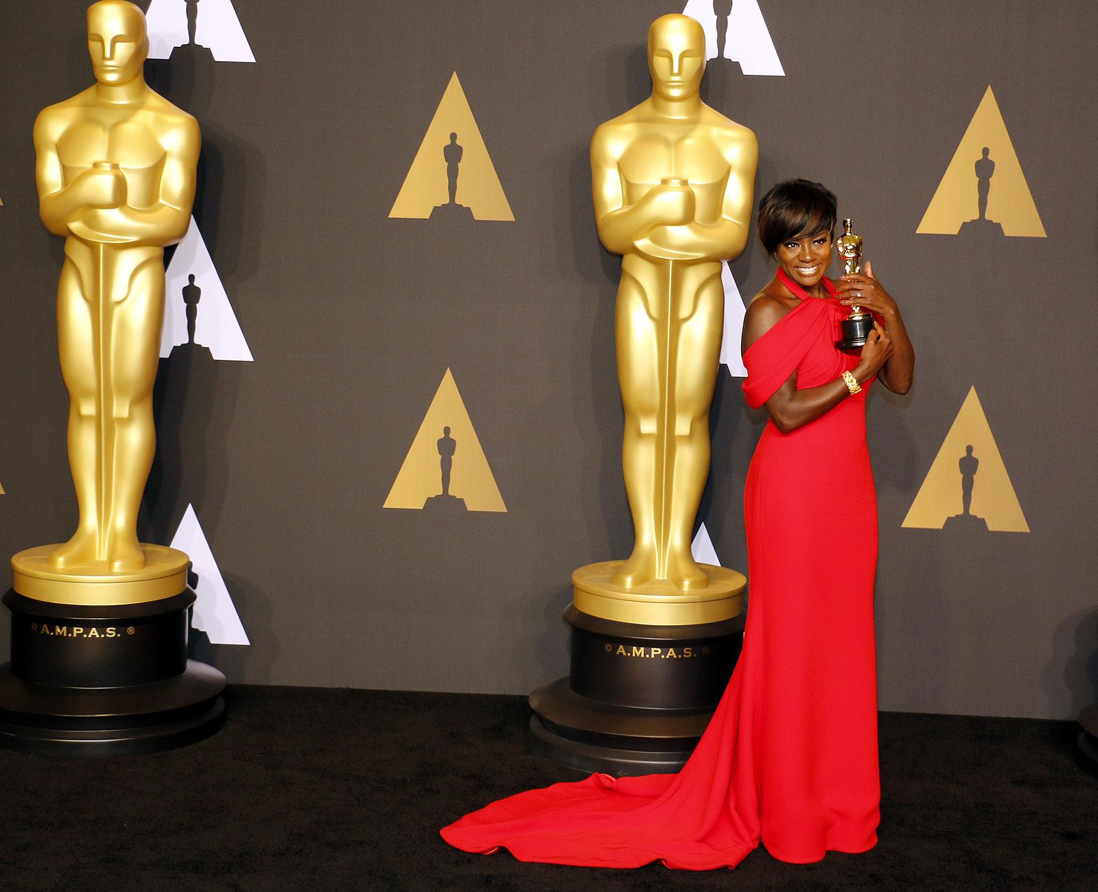 Viola Davis receiving an oscar award with a long red dress.