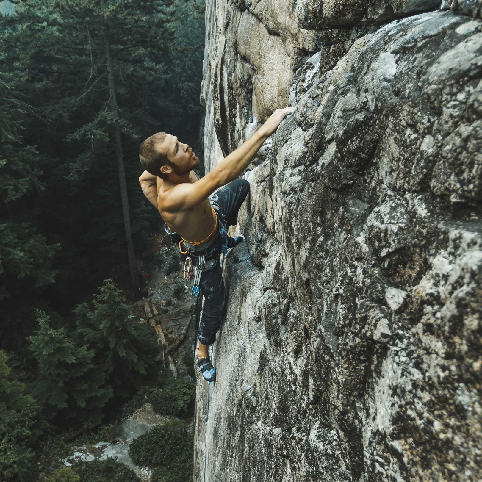 Man rock climbing while wearing the Nelson Pant