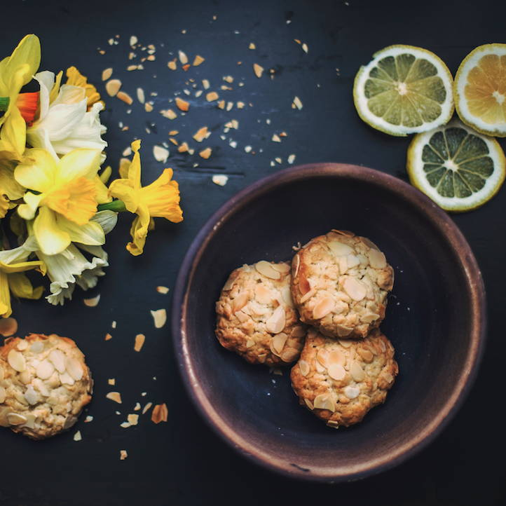 a bowl of  cookies with yellow flowers on the table