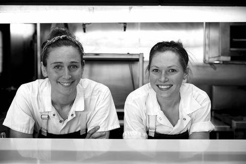 two chefs standing in a kitchen smiling at the camera