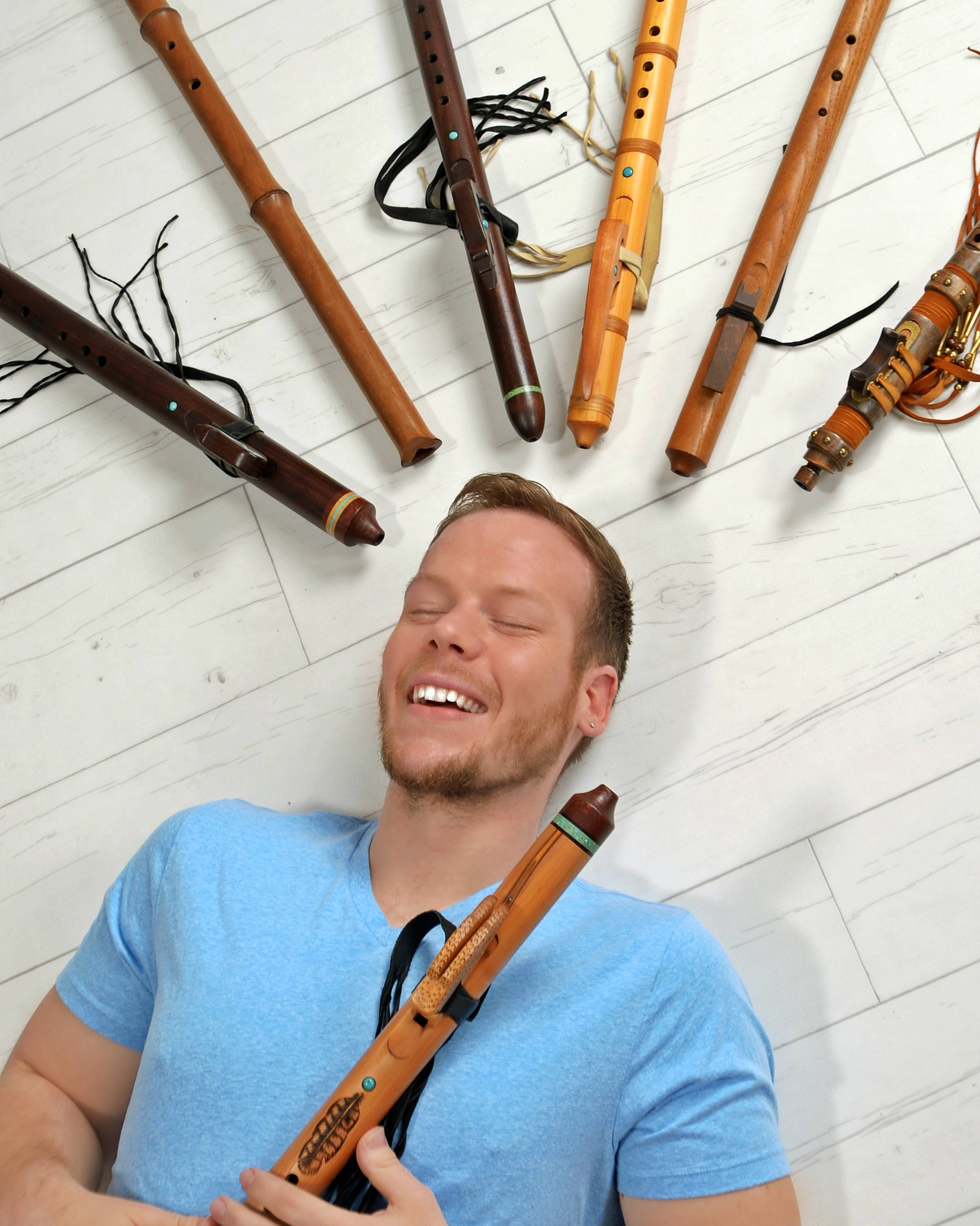 Jonny Lipford laying on the flute surrounded by Native American Flutes in gratitude
