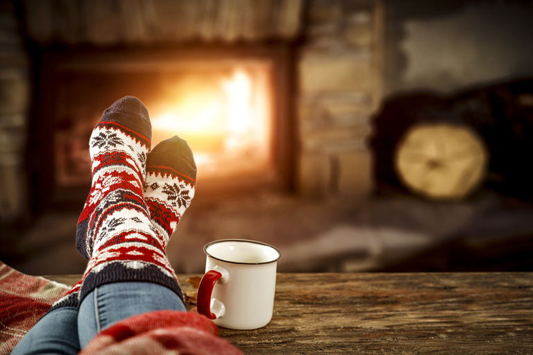 thick and cozy winter socks up on a table next to a coffee mug and in front of a warm fire
