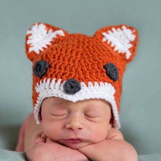 preemie baby wearing fox hat for first Halloween in the NICU