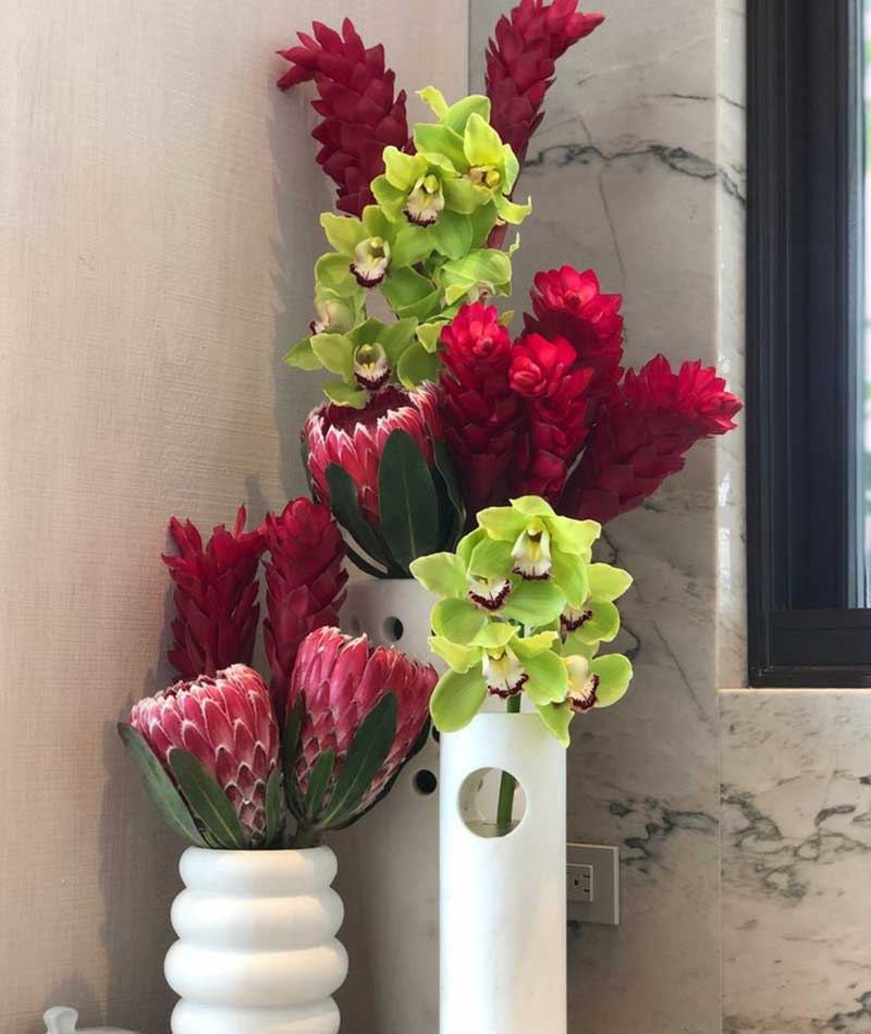 Group of tropical flowers in red and green placed on a corner table