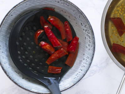 Place the strainer/colander of boiled dried chillies in another bowl of clean water to further remove excess seeds.