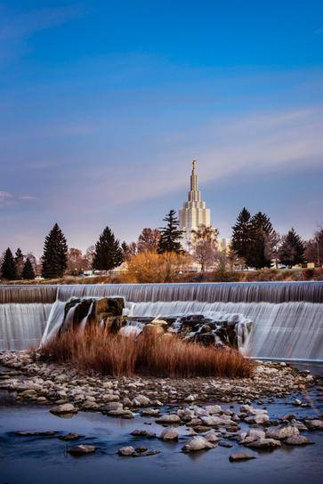 Distant photo of the Idaho Falls Temple with a calm waterfall in the foreground.