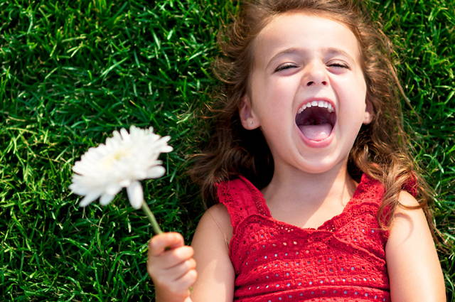 girl lying on the grass with flower and a smile