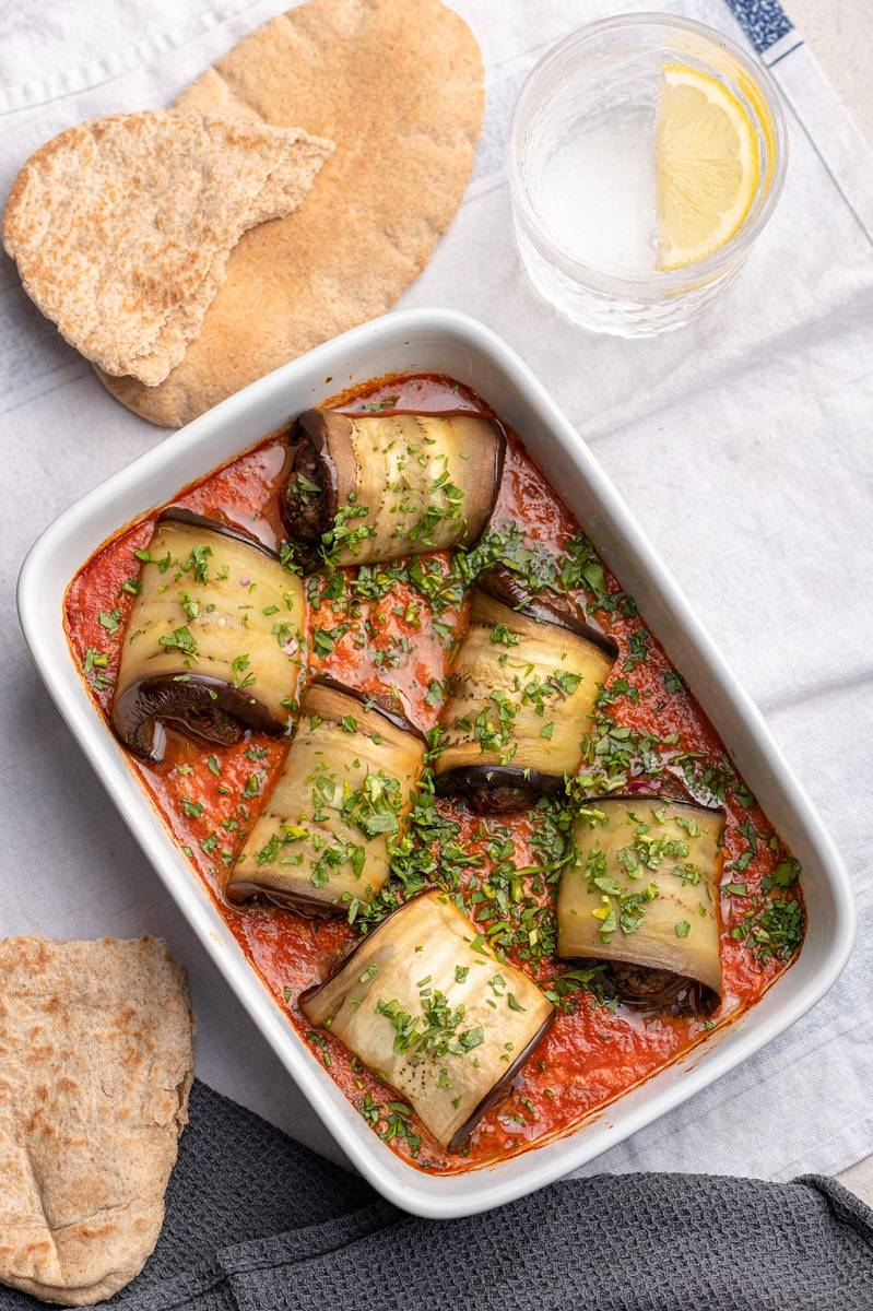 Aubergine kofta rolls sprinkled with parsley and served with pita bread