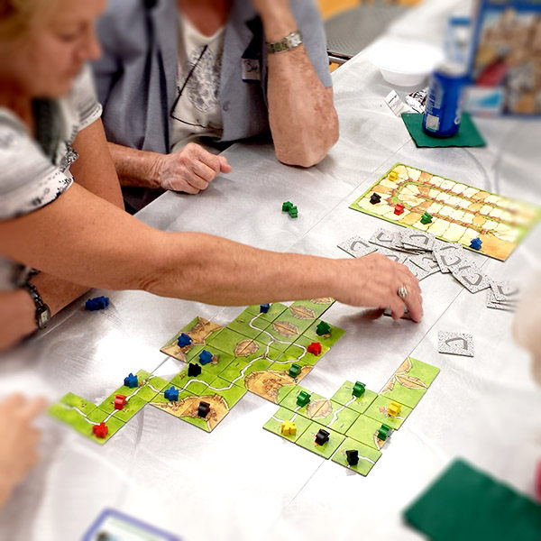 Images of people playing a board game at the library