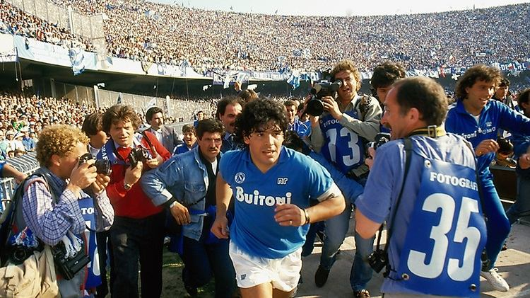 Footballer Diego Maradona running into a packed stadium surrounded by photographers.