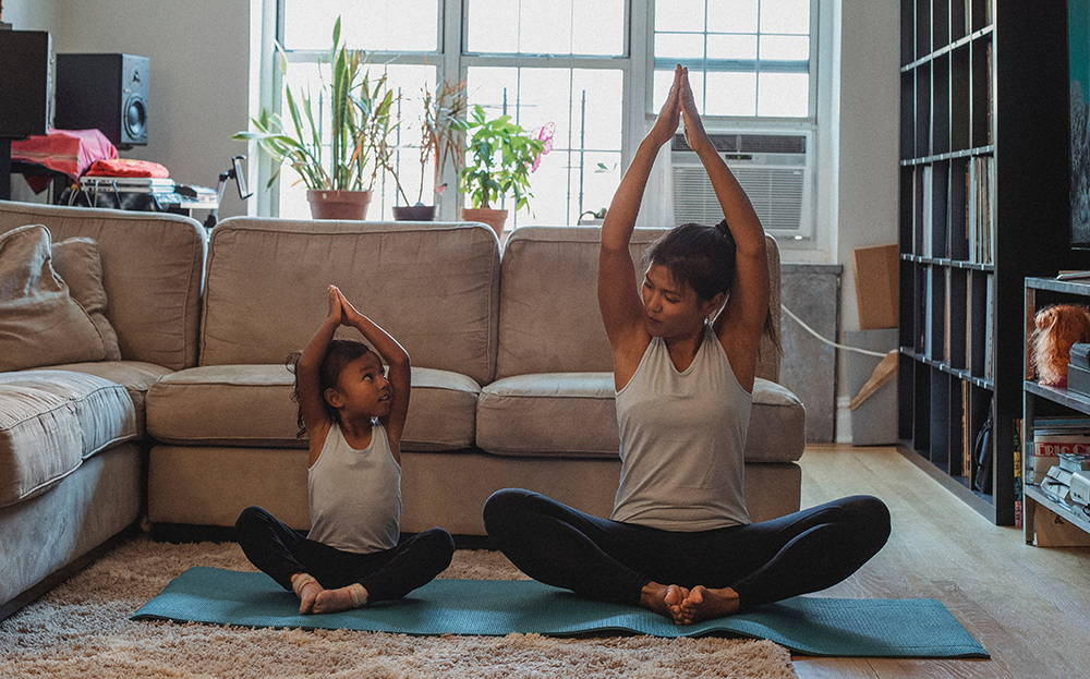 Mother and daughter doing a yoga pose together