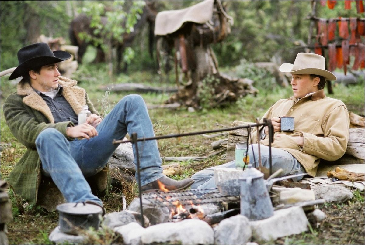 Jack and Ennis from Brokeback Mountain sitting at a campfire talking with a cup in their hands relaxed.