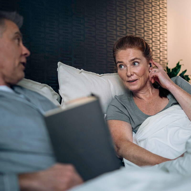 couple. in bed with earbud user adjusting the mode