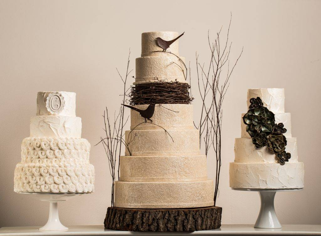Three large wedding cakes designed by the House of Clarendon in Lancaster, PA. The center cake features a bird's nest design and all three cakes feature off-white buttercream and fondant icing.
