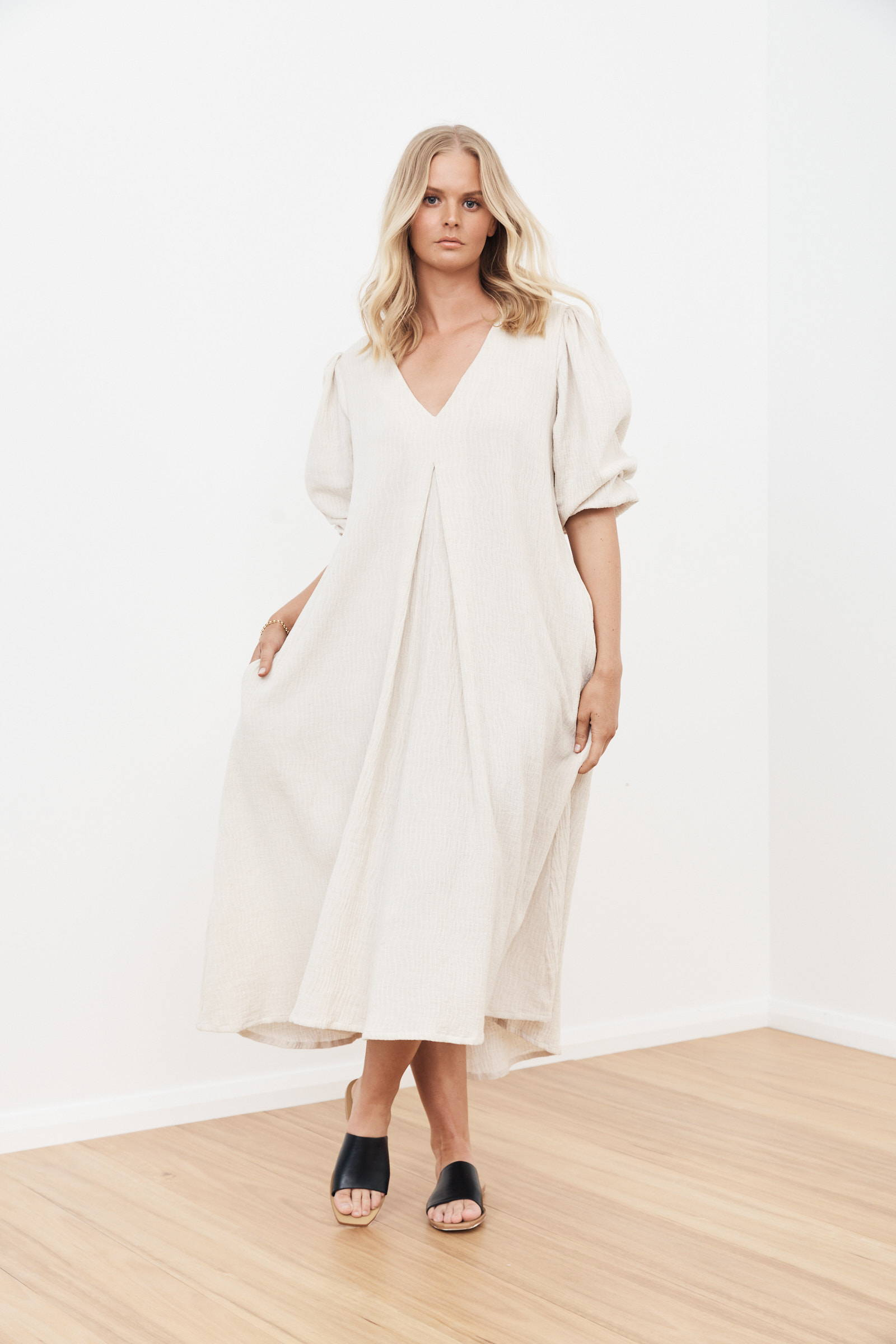 woman with shoulder length blonde hair not smiling wearing puff sleeve wide loose linen dress and black slide shoes